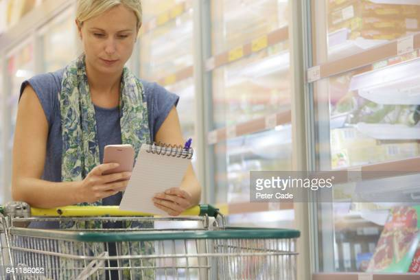 Woman with shopping trolley looking at phone and list