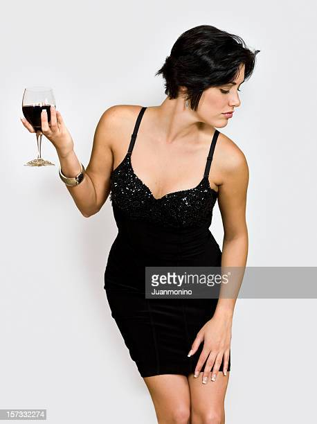 Woman with short hair in a party dress holding a wine glass