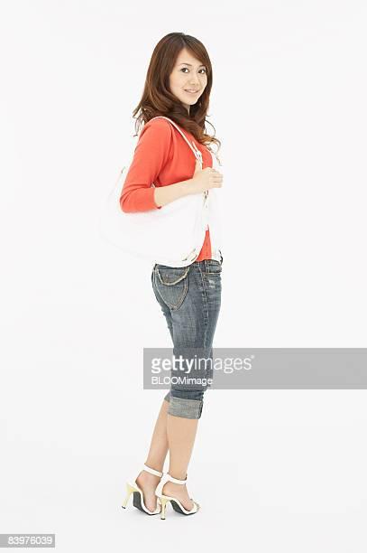 Woman with shoulder bag, studio shot