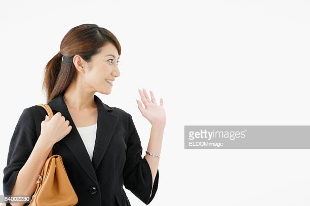 Woman with shoulder bag, waving, studio shot