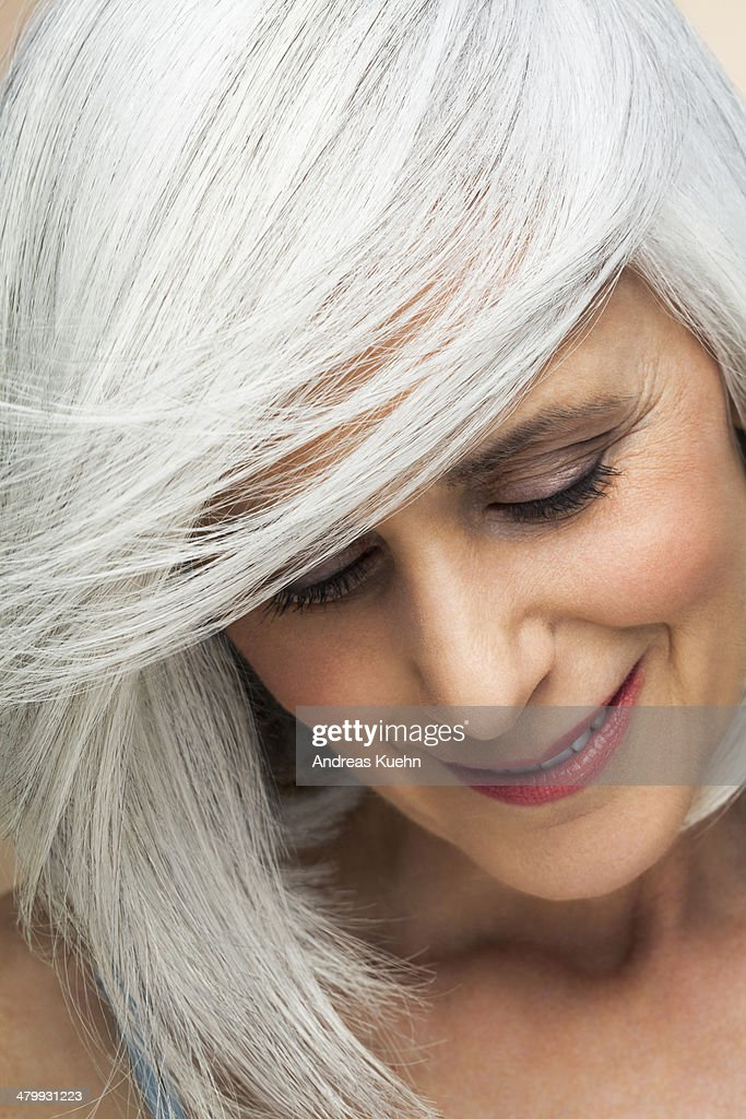 Woman with silvery, grey hair looking down.