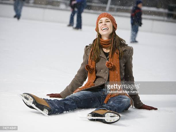Woman with skates sitting on ice smiling