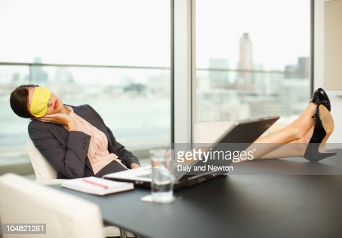Woman with sleep mask sleeping with feet up on conference room table : Bildbanksbilder