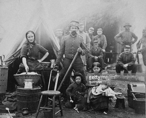 Woman with sleeves rolled up holding basket posed in front of tent with a soldier and three children other soldiers in the background 1862 31st...