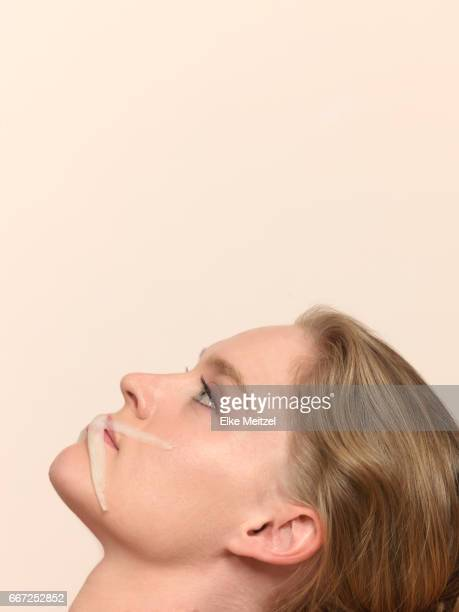 woman with slices of vegetables on her mouth