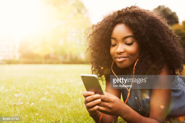 Woman with smart phone and headphones on grass
