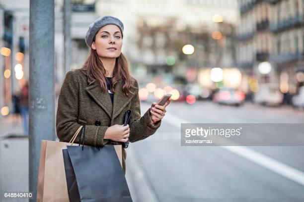スマート フォンや通りでショッピング バッグを持つ女性