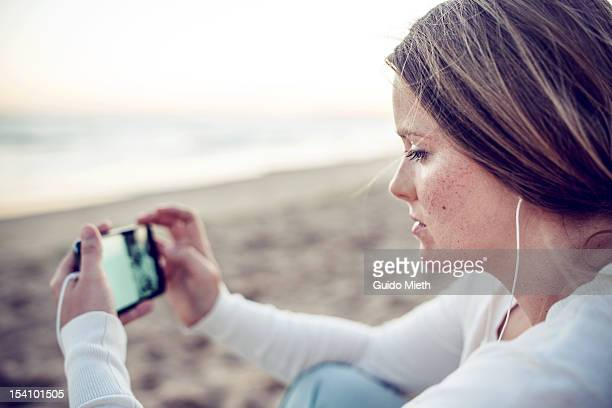 Woman with smart phone at beach.