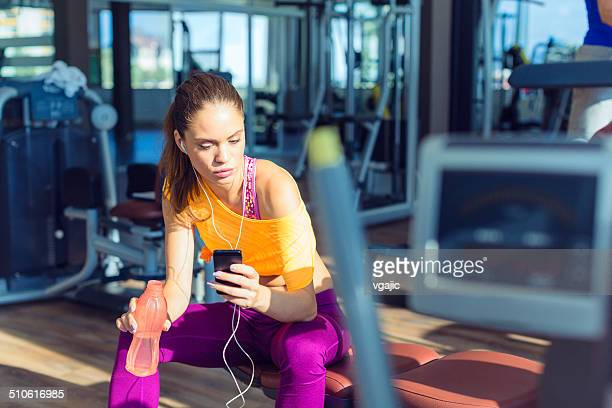 Woman with smart phone in gym.