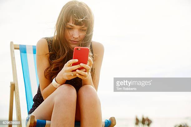 Woman with smart phone on beach.