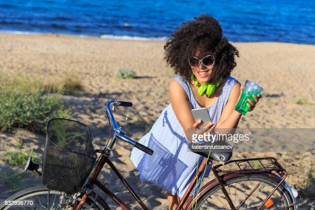 Woman with smart phone riding on sand