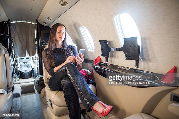 Woman with smart phone sitting in private jet airplane