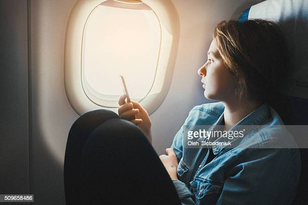 Woman with smartphone in airplane