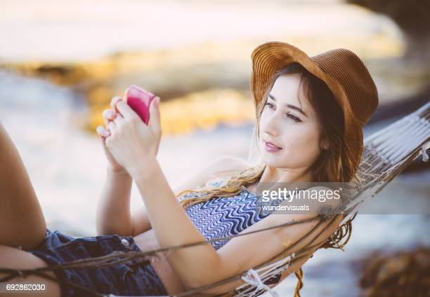 Woman with smartphone relaxing in a hammock at the beach