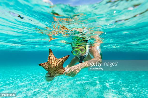 woman with snorkel and mask holding a starfish