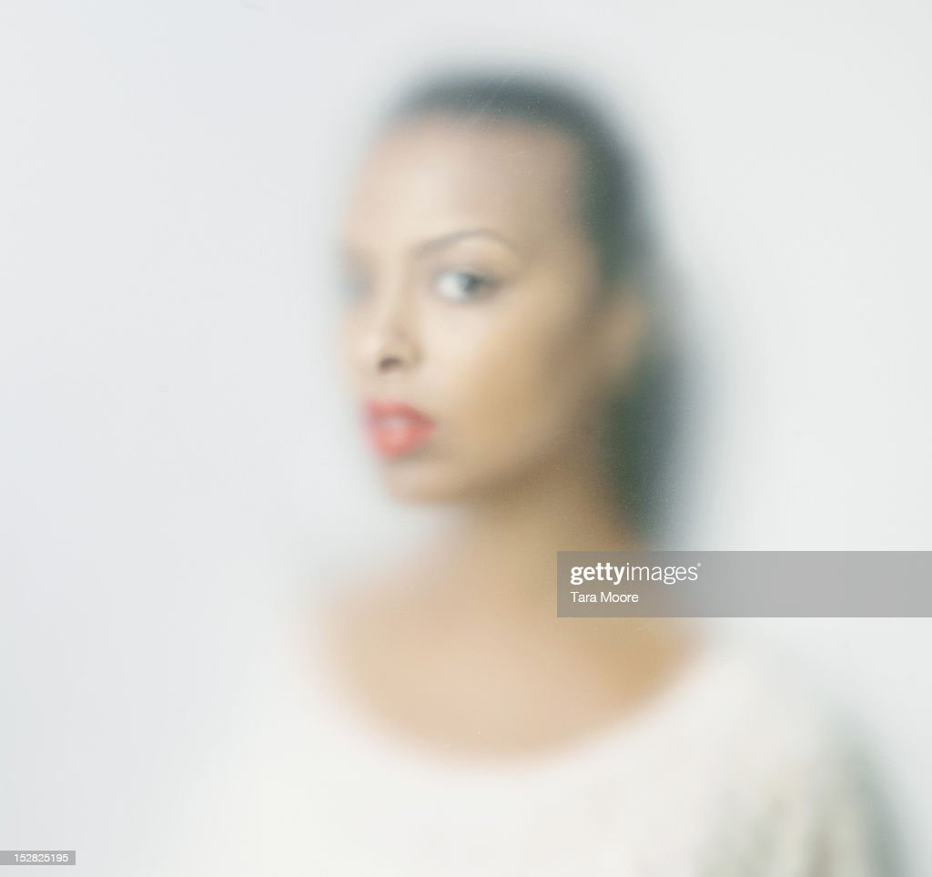 woman with soft focus looking through glass : Stock Photo