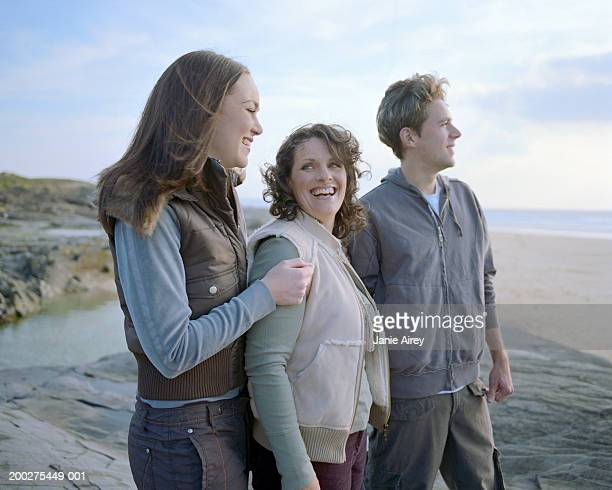 Woman with son and daughter (15-17) by sea, smiling