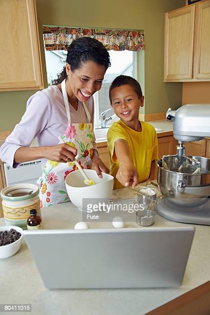 Woman with Son Looking at Laptop While Making Batter
