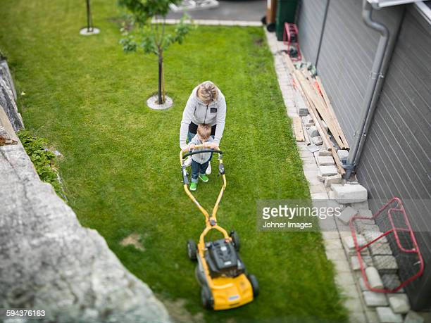 Woman with son mowing lawn