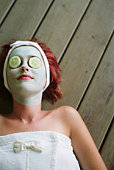 Woman with spa mask and cucumber slices