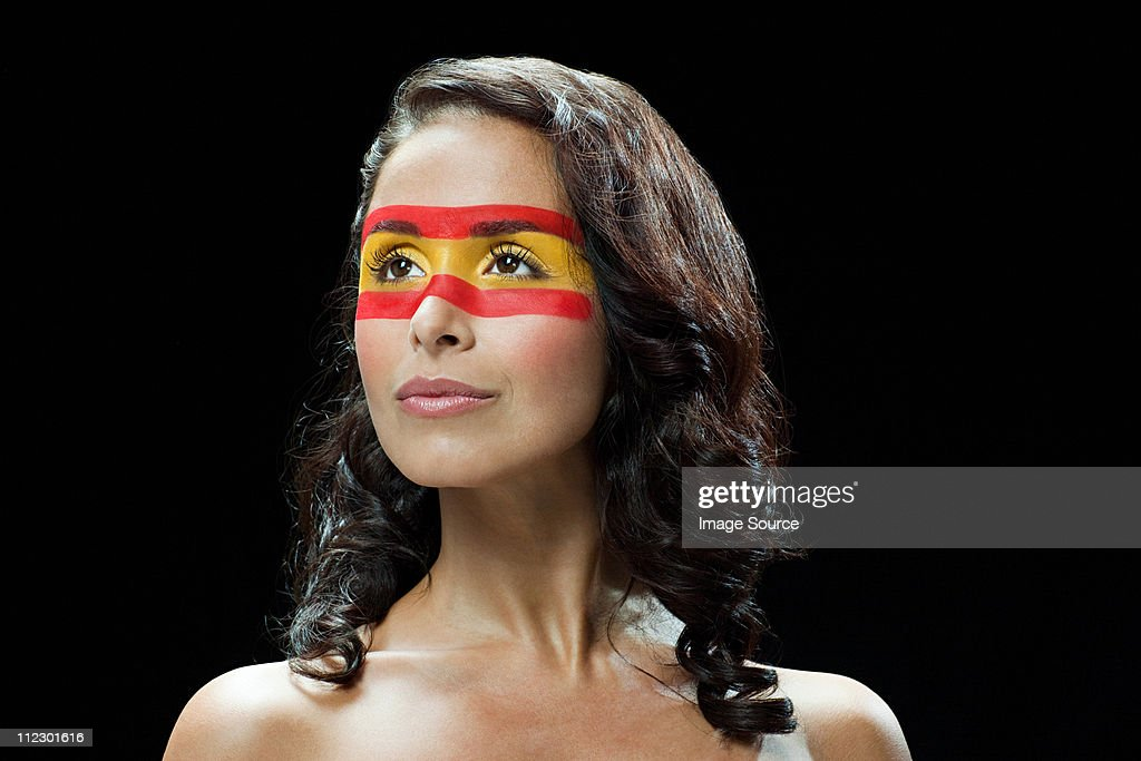 Woman with Spanish flag painted on face, looking away