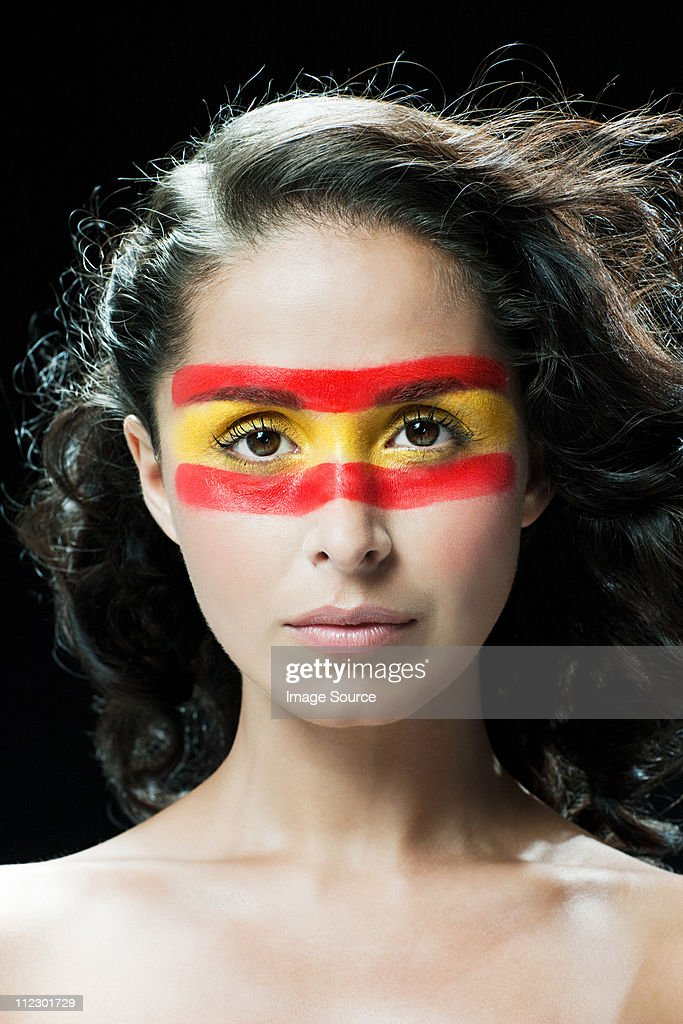 Woman with Spanish flag painted on face : Stock Photo
