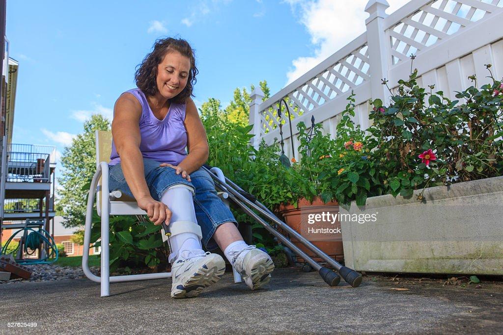 Woman with Spina Bifida adjusting leg brace so she can walk