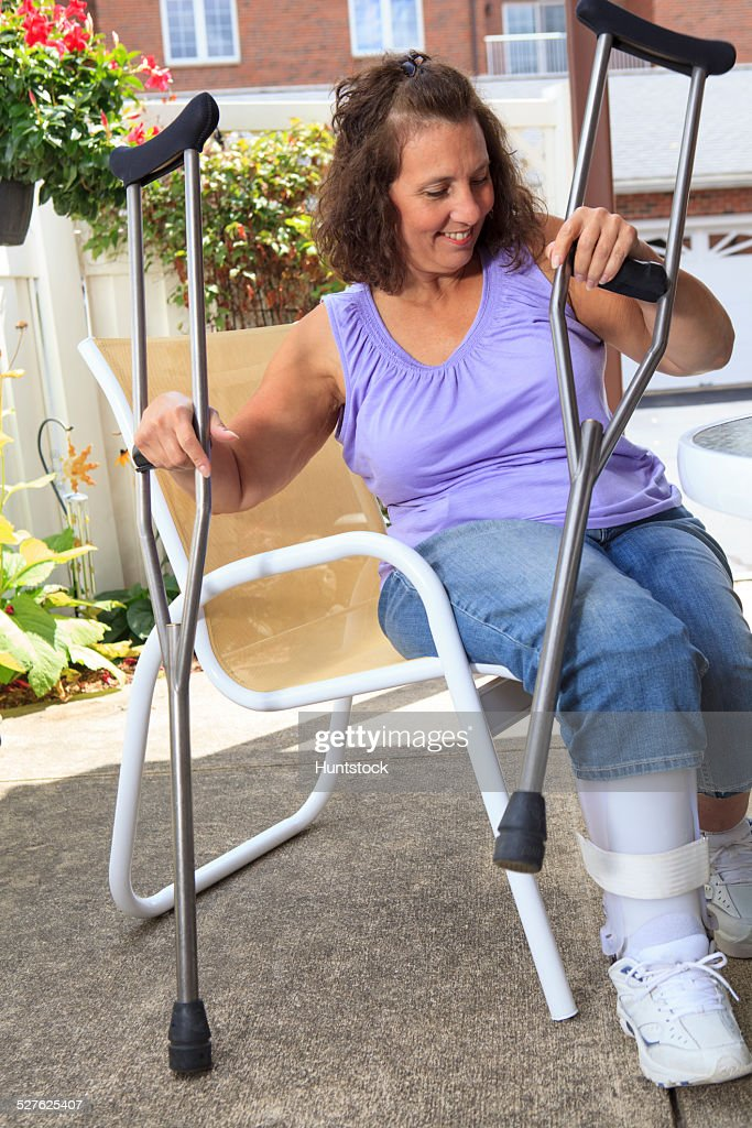 Woman with Spina Bifida getting up with crutches