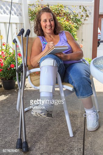 Woman with Spina Bifida writing notes while resting leg in a brace