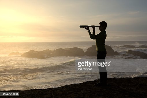 Frau mit Lupen mit Blick auf das Meer