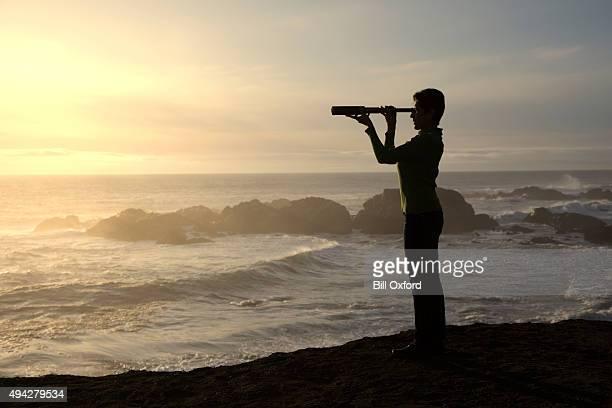Mujer con spyglass mirando hacia al mar