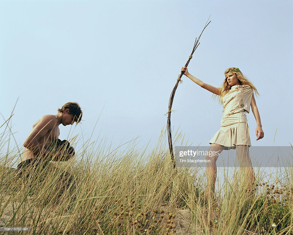 Woman with staff of twigs, man kneeling on ground holding pine cones : Stock Photo