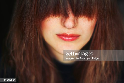 Woman with straight bangs covering her eyes : Stock Photo