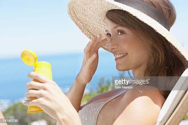 Donna con cappello di paglia applicando il blocco di sole a viso aperto