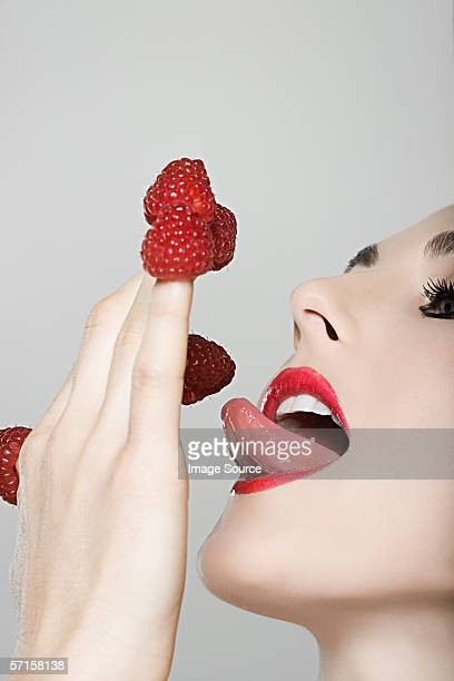 Woman with strawberries on her fingers