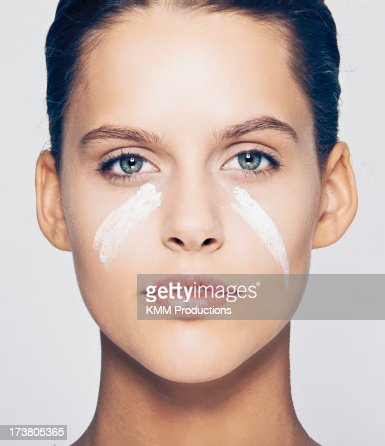 Woman with streaks of lotion on face : Stock Photo