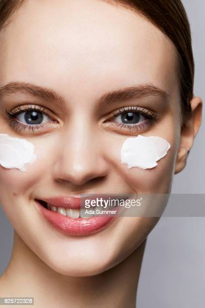 Woman with streaks of lotion on face