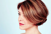 Close up portrait of sensual mature woman with elegant short haircut and natural makeup on blue background