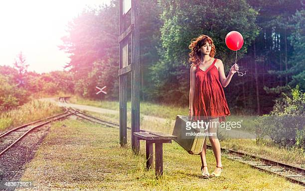 Woman with suitcase and balloon wait for a train