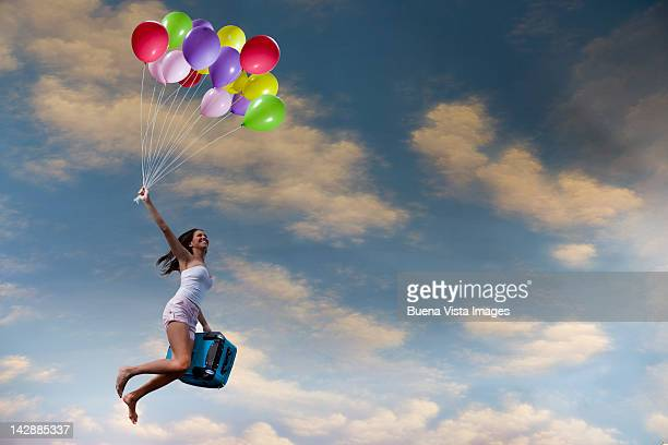 Woman with suitcase flying with balloons