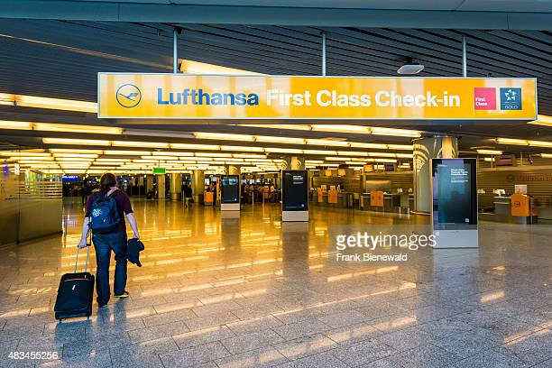A woman with suitcase is walking into the First Class Checkin of the airline Lufthansa at Terminal 1 of Frankfurt International Airport