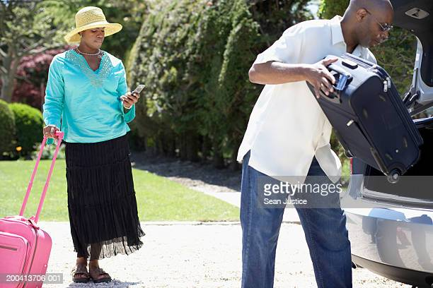 Woman with suitcase looking at cell phone near car, man loading trunk