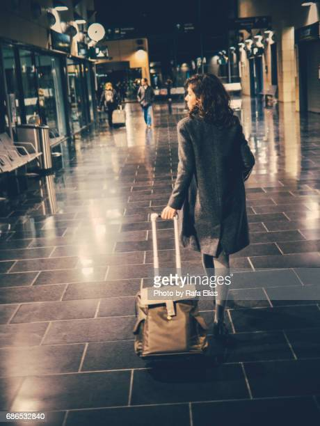 Woman with suitcase walking along train station