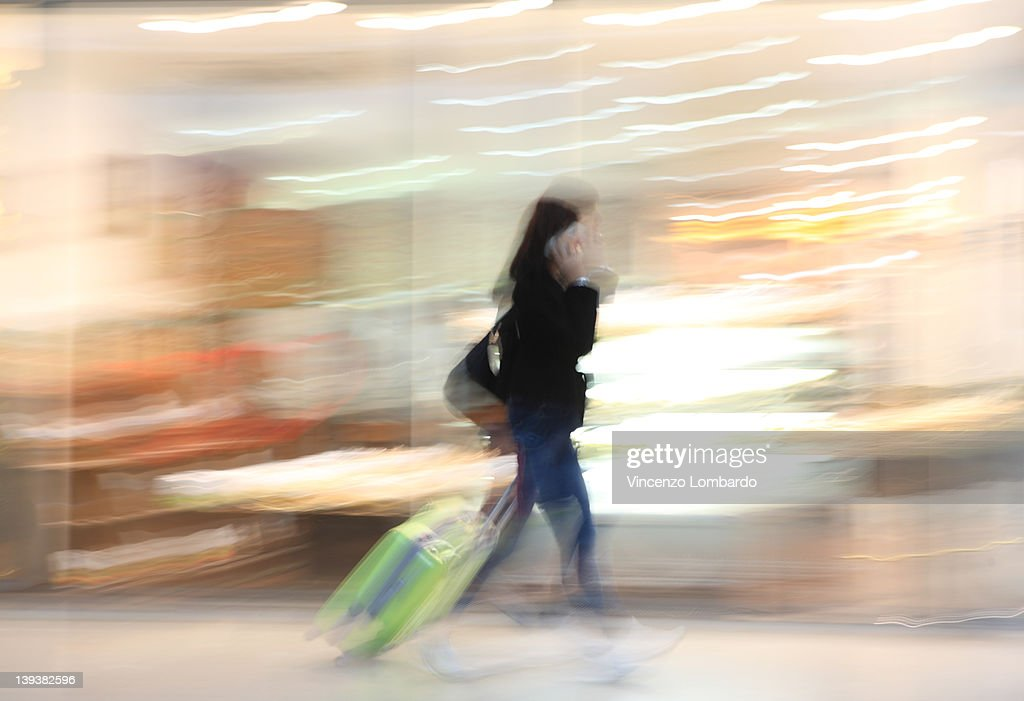 Woman with suitcase walking in an airport : Stock Photo
