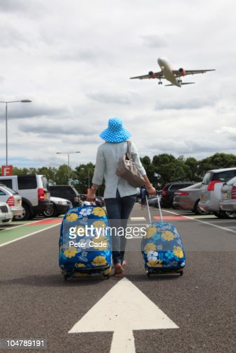 Woman with suitcases in airport car park : ストックフォト