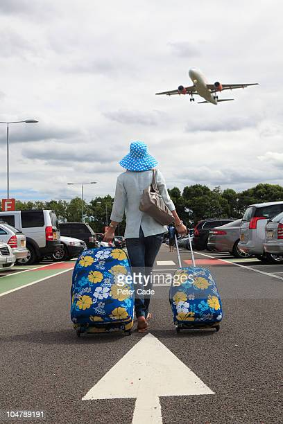 Woman with suitcases in airport car park