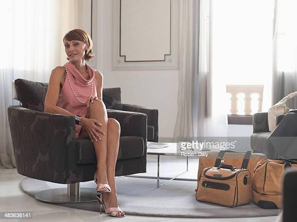 Frau mit Koffer sitzt in Wartebereich