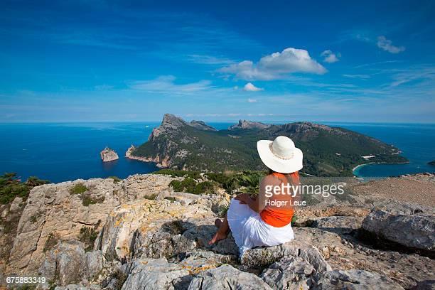 Woman with sun hat overlooks Cap de Formentor