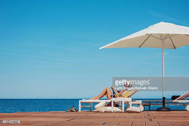 Woman with sun hat reading book at the seaside