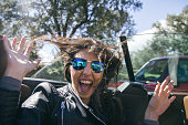 Woman with sunglasses and hands up in a convertible car